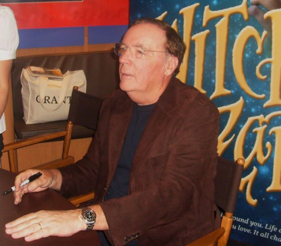 Writer James Patterson signing a book from the Witch and Wizard series